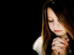 child-praying-black-background